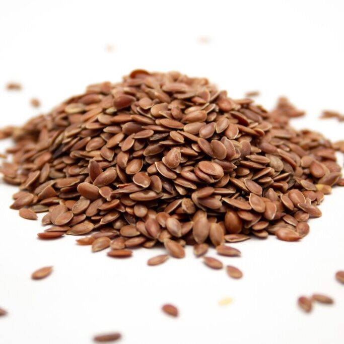 A closeup shot of flax seeds on a white surface